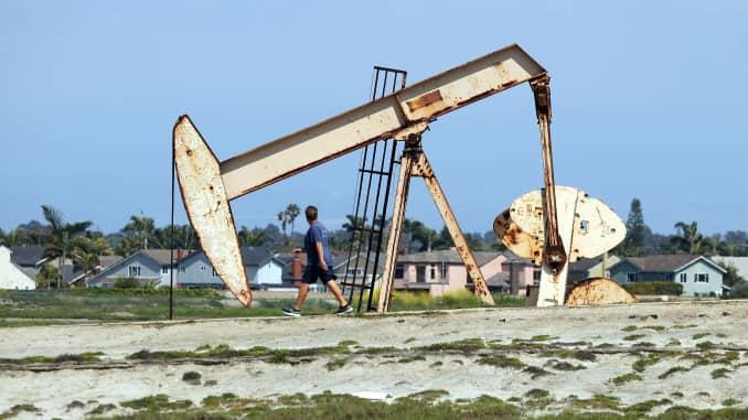 A man walks on a path in front of an oil derrick near the Huntington Beach Oil Fields on April 20, 2020 in Huntington Beach, California.
