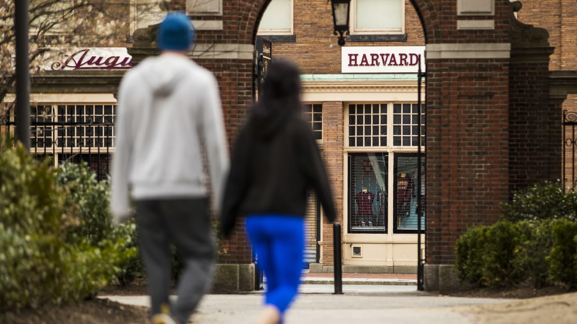 Pedestrians walk through Harvard Yard on the closed Harvard University campus in Cambridge, Massachusetts, U.S., on Monday, April 20, 2020.