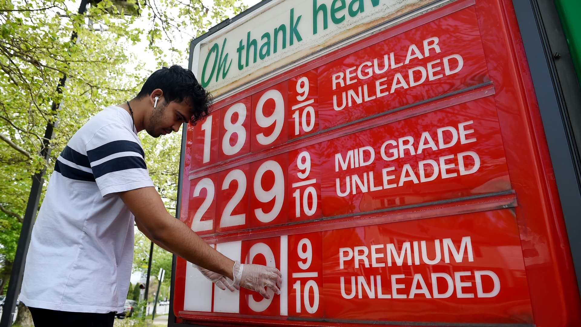An employee of a gas station adjusts gasoline pump prices as they continue to fall with the oil market in turmoil on April 21, 2020, in Arlington, Virginia.