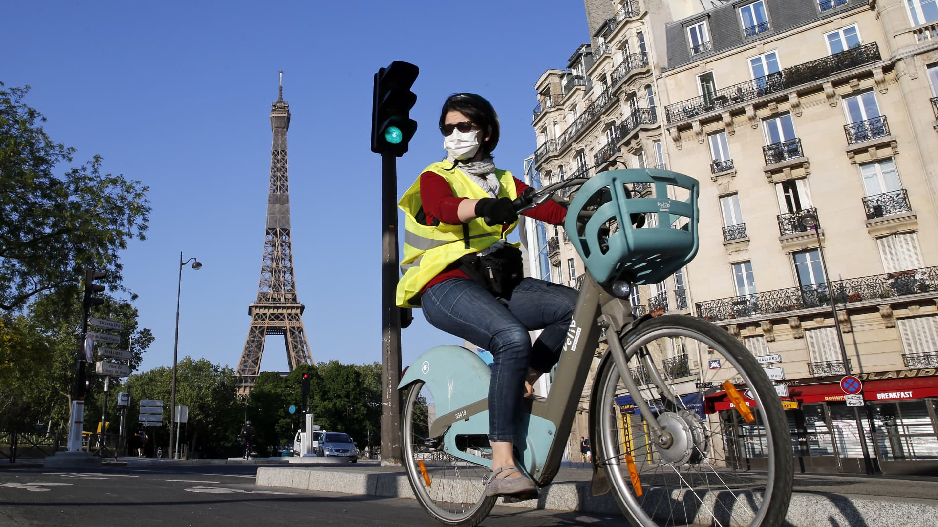 A woman wearing a protective mask rides her bicycle next to the Eiffel Tower on April 23, 2020 in Paris, France.