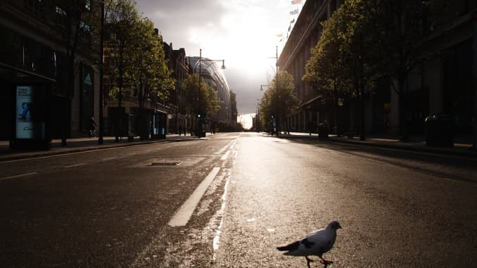 A pigeon walks across a deserted Oxford Street in London, England, on March 28, 2020.