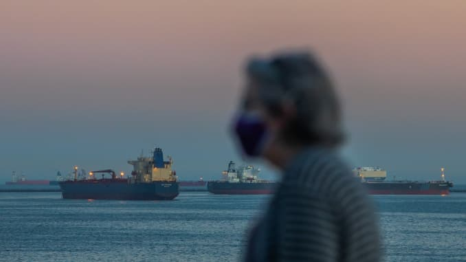 A woman wearing face mask walks on the ocean front while Oil tankers are seen anchored off the coast of Long Beach, California, after sunset on April 25, 2020.