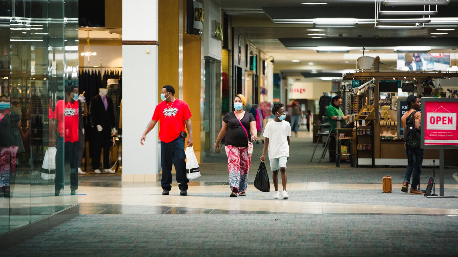 Shoppers wearing protective masks walk through the re-opened Anderson Mall in Anderson, South Carolina, on Friday, April 24, 2020.