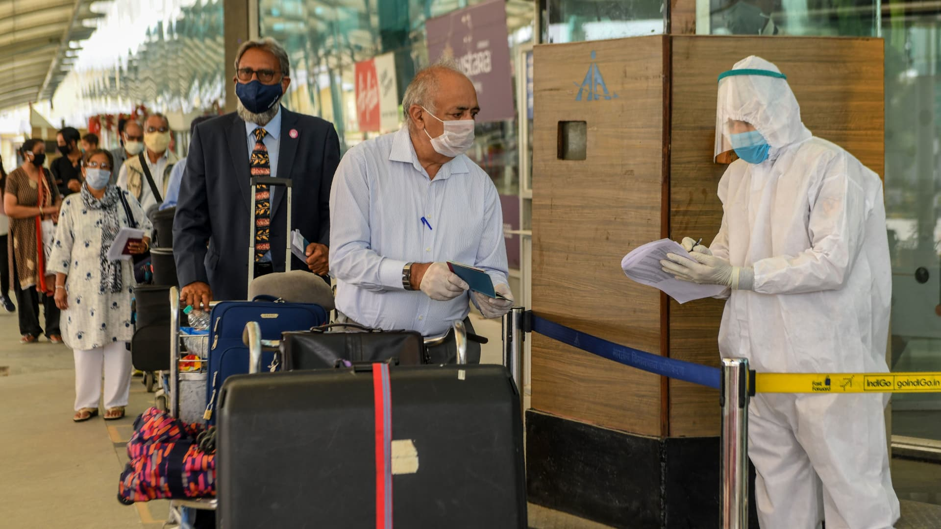 A security personnel wearing protective gear (R) checks the passports of British nationals before check-in for a special flight to London during a government-imposed nationwide lockdown as a preventive measure against the COVID-19 coronavirus, at the Sri Guru Ram Dass Jee International Airport in Amritsar on April 25, 2020.
