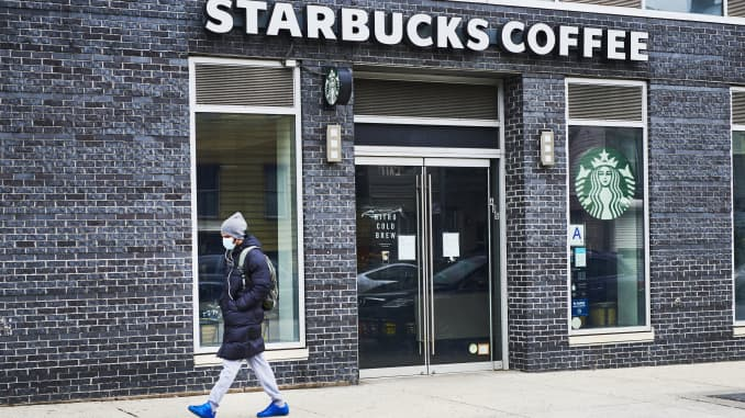 A pedestrian wearing a protective mask walks in front of a temporarily closed Starbucks coffee shop in the Brooklyn borough of New York, U.S., on Monday, April 27, 2020.