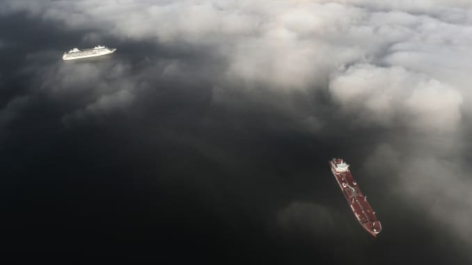 An aerial view shows a cruise ship (L) and tanker vessel anchored near the ports of Long Beach and Los Angeles amid the coronavirus pandemic on April 28, 2020 off the coast of Long Beach, California.