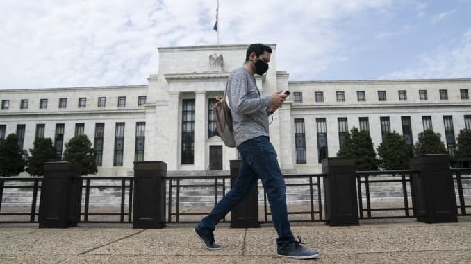 A man wearing a mask walks past the U.S. Federal Reserve building in Washington D.C., the United States, on April 29, 2020.