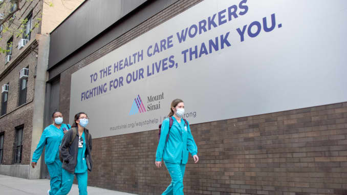 Medical workers wearing masks walk past a 'Thank You' sign outside of Mount Sinai Hospital amid the coronavirus pandemic on May 3, 2020 in New York City.