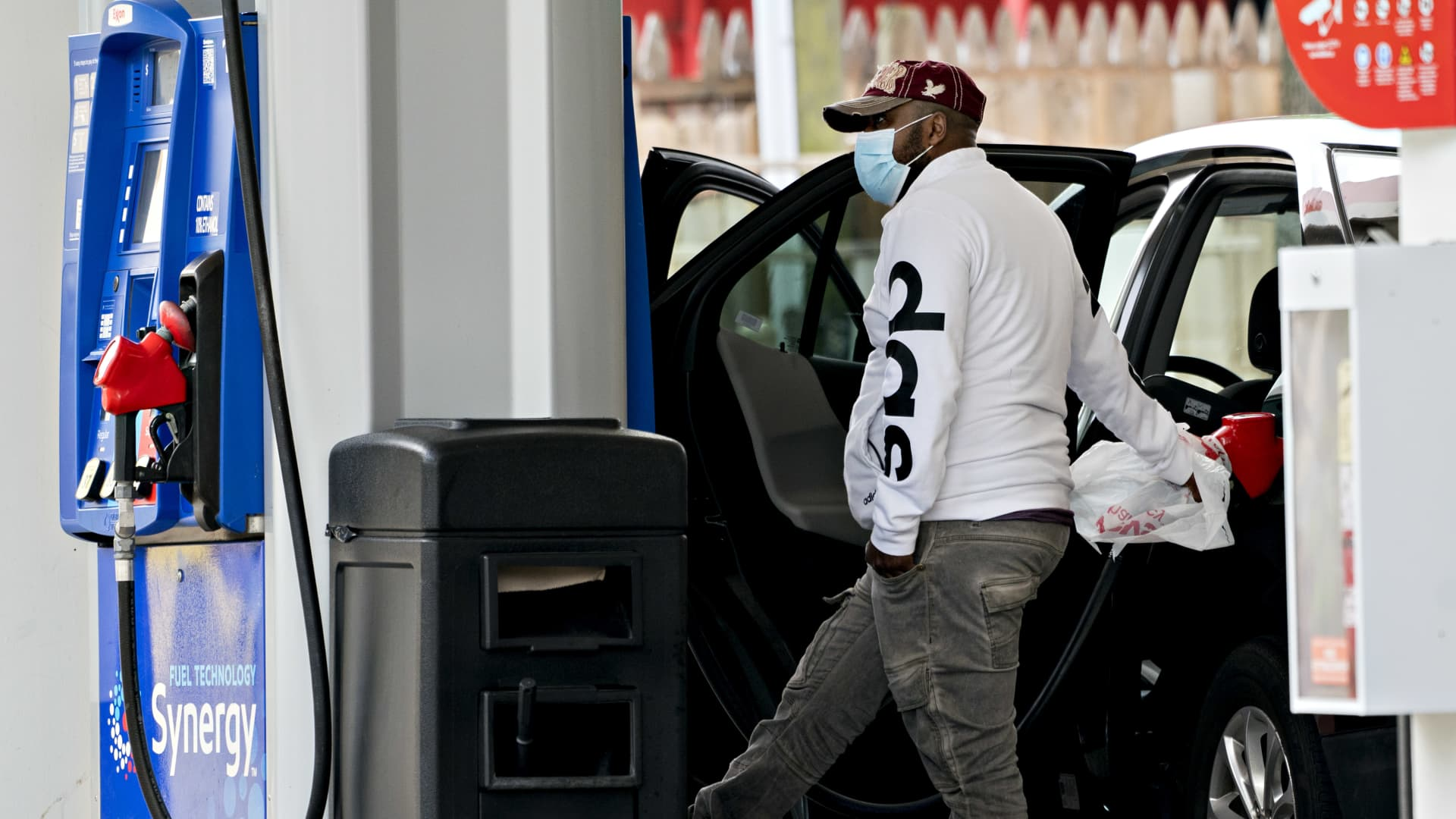 A customer wearing a protective mask uses a plastic shopping bag to hold a fuel nozzle while refueling a vehicle at an Exxon Mobil Corp. gas station in Arlington, Virginia.