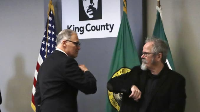 Washington Governor Jay Inslee, left, gives a elbow touch to American Sign Language interpreter Terry Dockter after a news conference about the coronavirus outbreak.