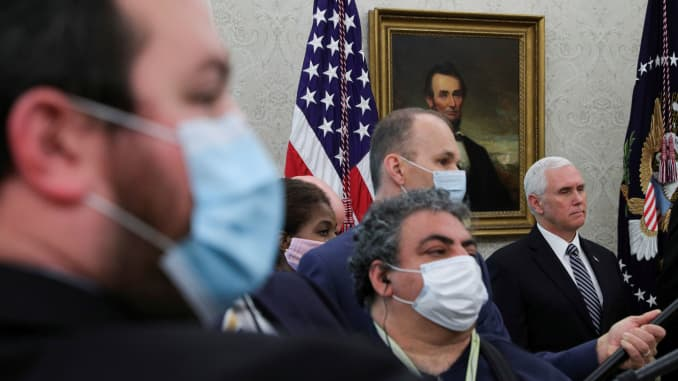 Vice President Mike Pence stands among television soundmen, radio reporters and other media personnel all wearing protective masks