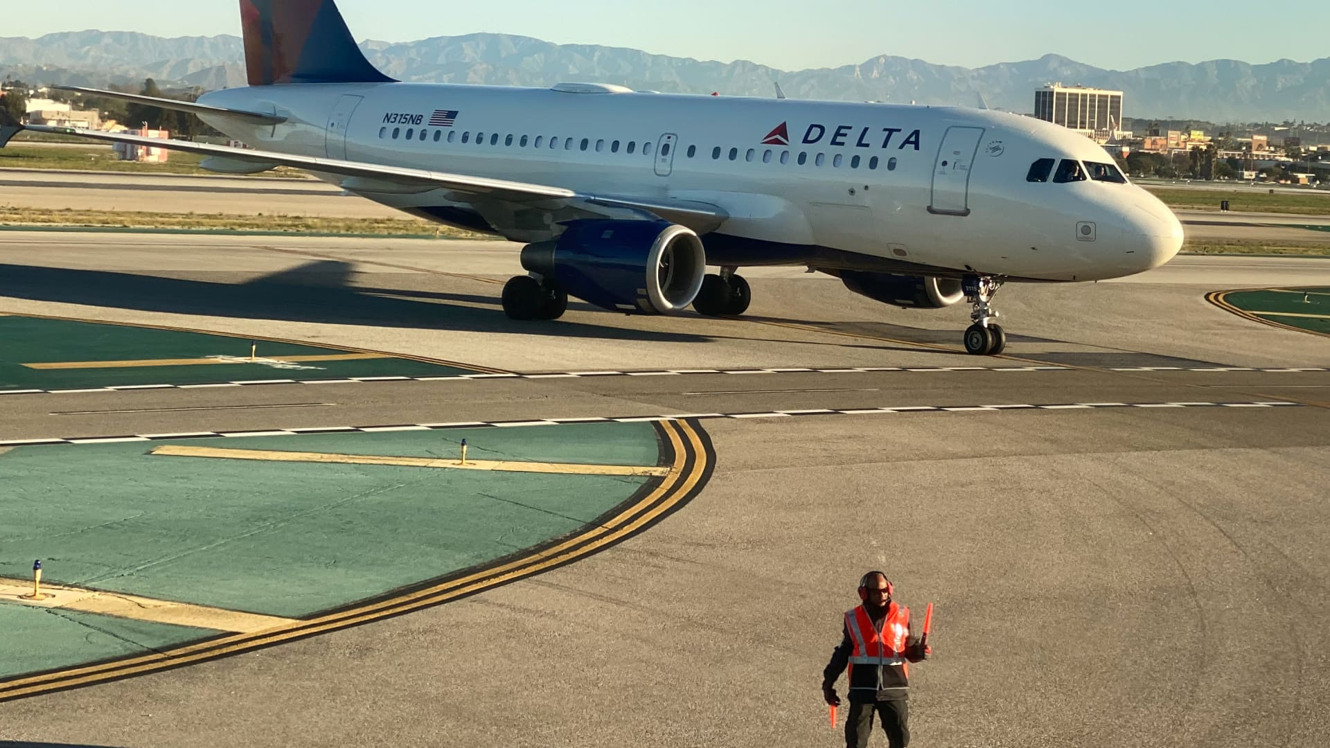 An airport worker guides a Delta Air Lines Airbus A319-100 plane on the tarmac at LAX in Los Angeles, California, U.S., January 6, 2020.