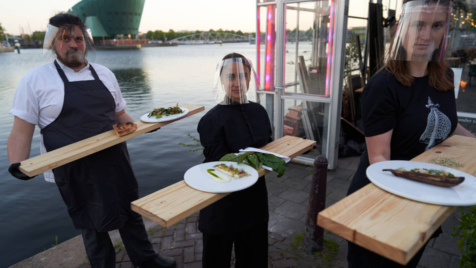 Waiters wear face shields and gloves and rely on long wooden boards to serve diners.