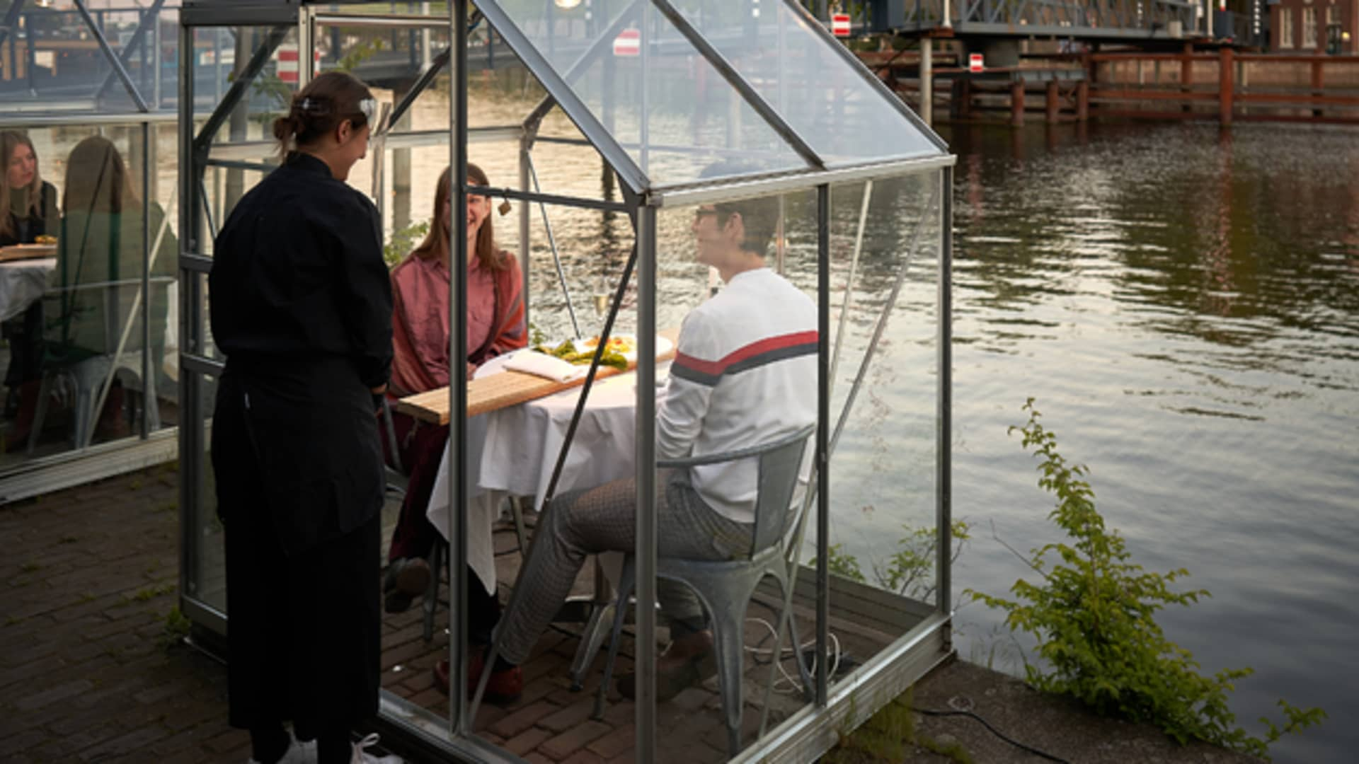 A server at Mediatic ETEN uses a wooden board to serve food to diners inside a greenhouse.