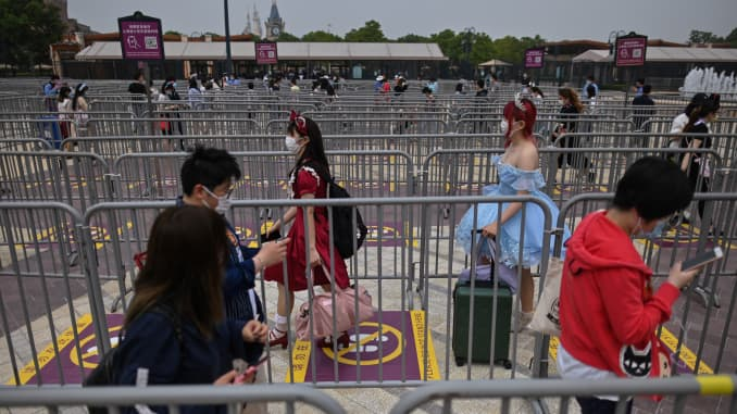 People wearing face masks maintaining social distancing as they enter the Disneyland amusement park in Shanghai on May 11, 2020.