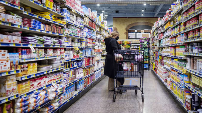 A shopper wearing a protective mask walks down an aisle at a grocery store in Chicago, Illinois, U.S., on Thursday, May 7, 2020.