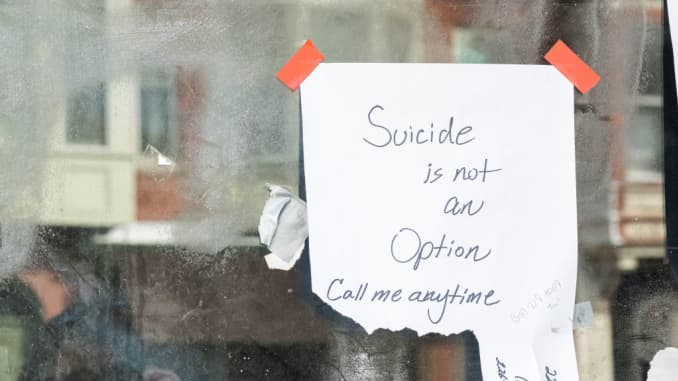 """A sign in an abandoned storefront says, """"Suicide is Not An Option Call Me Anytime' in the hope of helping people with despair during this time."""