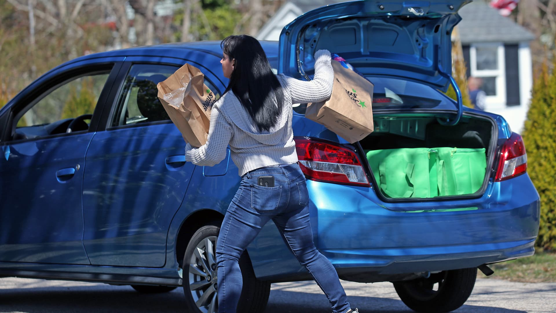 FALMOUTH, MA - APRIL 8: Instacart shopper Loralyn Geggatt makes a delivery to a customer's home during the COVID-19 pandemic in Falmouth, MA on April 7, 2020. Some Amazon, Instacart and other workers protested for better wages, hazard pay and sick time. (Photo by David L. Ryan/The Boston Globe via Getty Images)