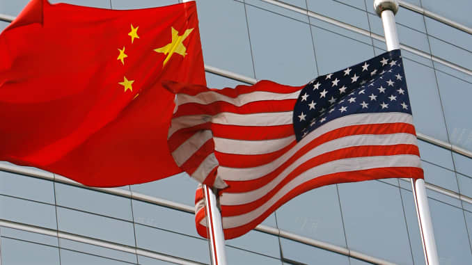 The national flags of the U.S. and China waving outside a building.