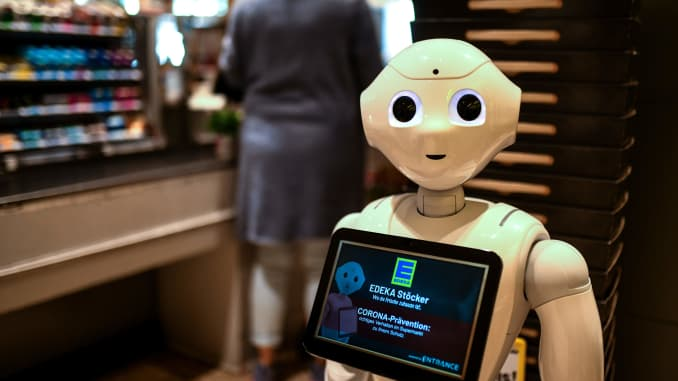 "Humanoid robot ""Prepper"" stands on April 2, 2020 at the cash desk of a supermarket of the Edeka retail chain in Lindlar, Germany, to explain protective measures and to promote solidarity with each other, amid the novel coronavirus / COVID-19 pandemic."