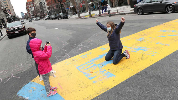 Lisa Wyman, a marathon runner who has run the Boston Marathon every year since 2002, has her photo taken at the finish line by her children Alex and Anderson, 5 and 7 years old, on what would have been Marathon Monday, April 20, 2020 on Boston's Boylston