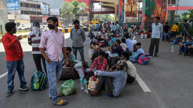 Migrant workers and families wait for transport to go back to their native places after the goverment eased a nationwide lockdown imposed as a preventive measure against the COVID-19 coronavirus, in Ghaziabad on May 16, 2020.