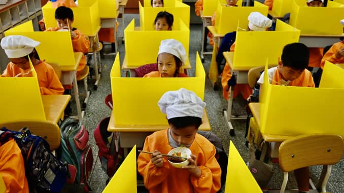 Students eat their lunch on desks with plastic partitions as a preventive measure to curb the spread of the coronavirus at Dajia Elementary School in Taipei, Taiwan on April 29, 2020.