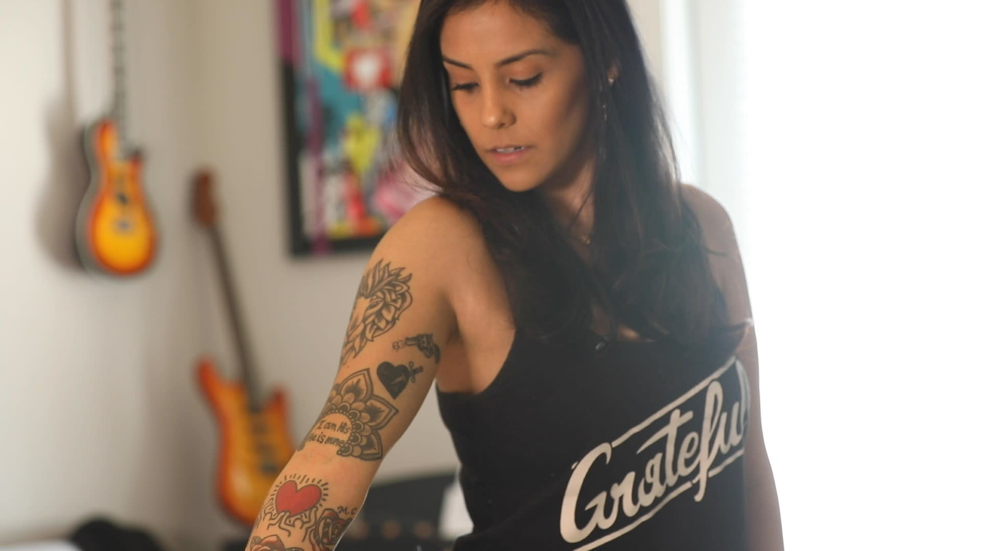 Andrea Contreras reflects on her tattoos in her apartment in Austin, Texas.