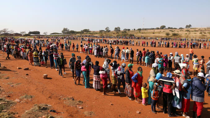 People stand in a queue to receive food aid amid the spread of the coronavirus disease (COVID-19), at the Itireleng informal settlement, near Laudium suburb in Pretoria, South Africa, May 20, 2020.