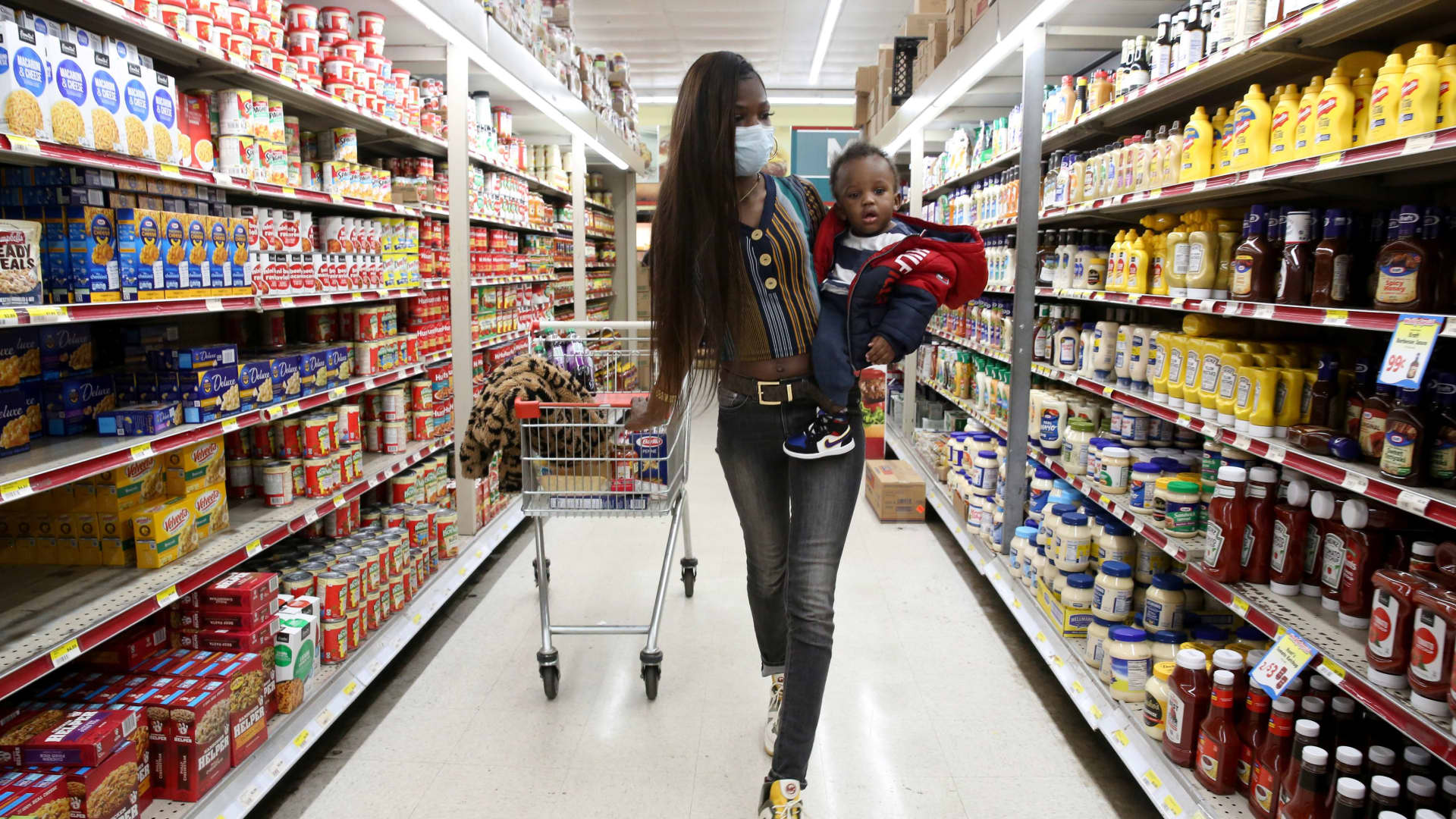Mic'Kale Smith, who works as a security guard but has had to take time off to care for her son during the coronavirus disease (COVID-19) outbreak, wears a face mask as she shops with her son Da'Mier at the Tiger Market in Oxon Hill, Maryland, May 20, 2020.