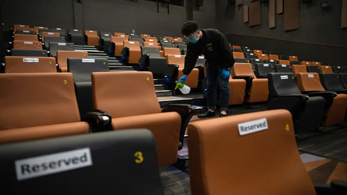 A worker wearing a protective mask sprays disinfectant inside a theater at the K11 Art House cinema operated by UA Cinema Circuit Ltd. in Hong Kong, China, on Friday, May 8, 2020.