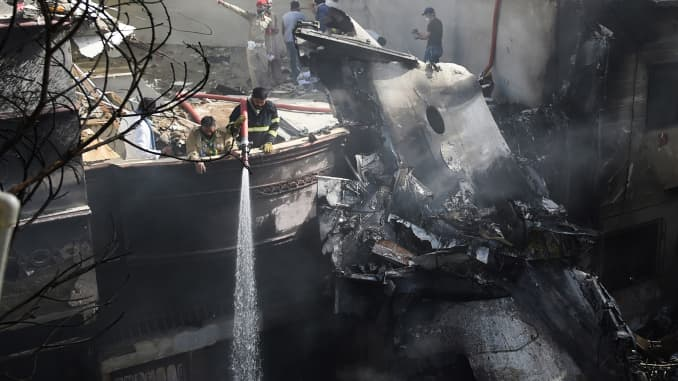 Firefighters spray water on the wreckage of a Pakistan International Airlines aircraft after it crashed at a residential area in Karachi on May 22, 2020. A Pakistani passenger plane with nearly 100 people on board crashed into a residential area of the so