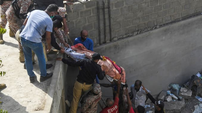 Rescue workers move a body from the site after a Pakistan International Airlines aircraft after crashed at a residential area in Karachi on May 22, 2020.