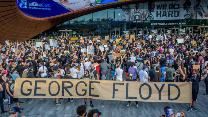 Protesters holding a giant banner reading GEORGE FLOYD outside the Barclays Center.