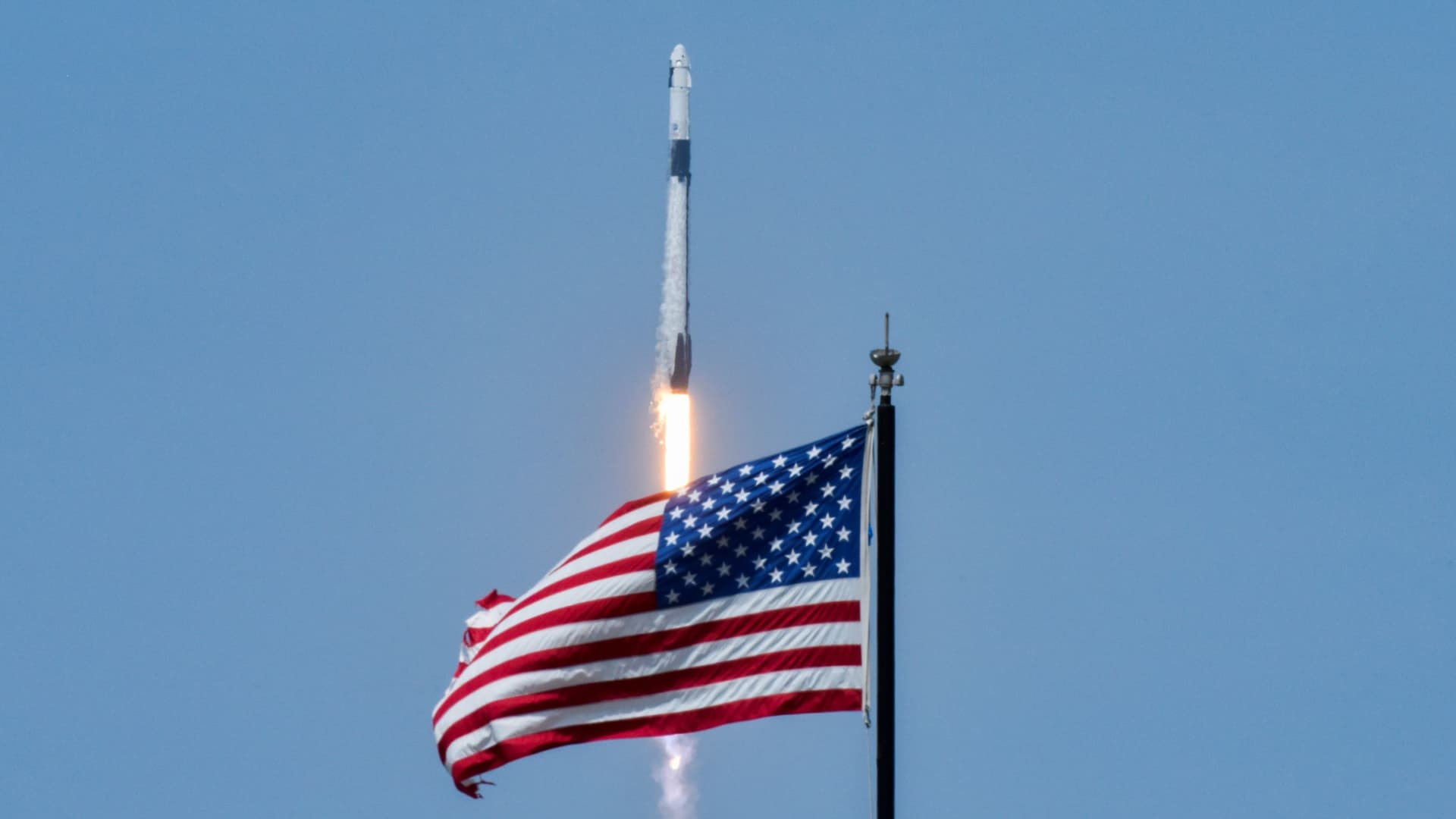 An American flag is seen as SpaceX Falcon 9 rocket and Crew Dragon spacecraft carrying NASA astronauts Douglas Hurley and Robert Behnken lifts off during NASA's SpaceX Demo-2 mission to the International Space Station from NASA's Kennedy Space Center in Cape Canaveral, Florida, U.S. May 30, 2020.