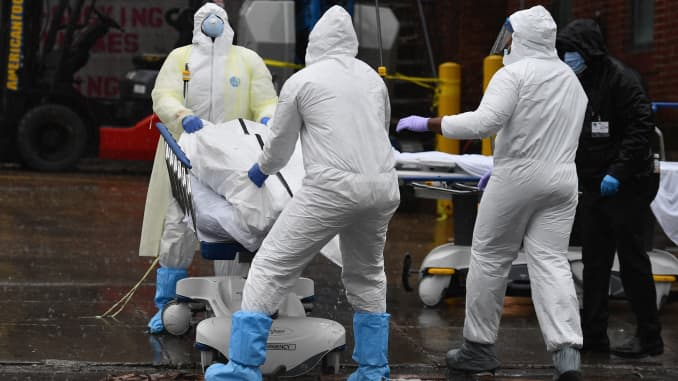 Medical personnel move a deceased patient to a refrigerated truck serving as make shift morgues at Brooklyn Hospital Center on April 09, 2020 in New York City.