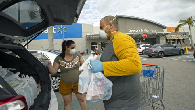 Joel Porro and Lizz Hernandez wear gloves and protective masks as they put bags in the trunk of their car after shopping at Walmart Supercenter as the coronavirus pandemic continues, March 5, 2020 in Miami.