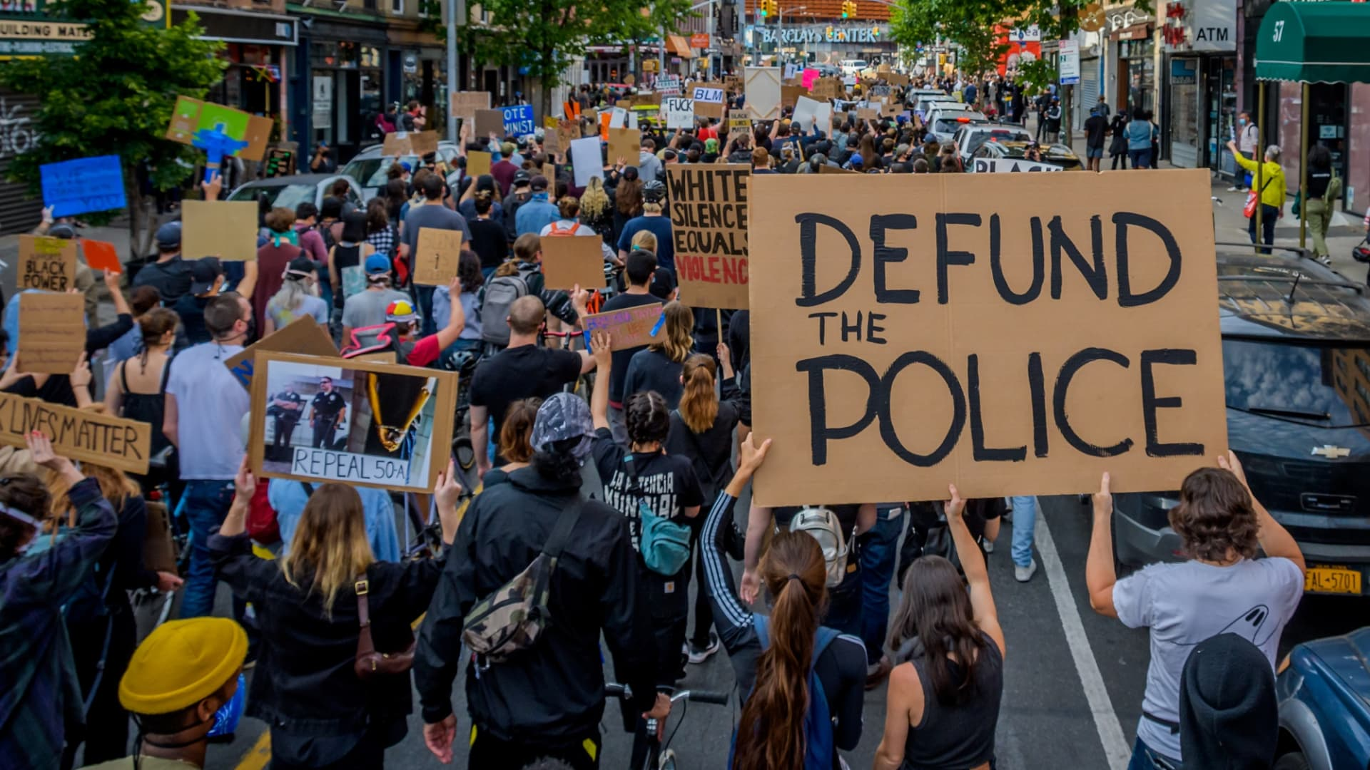 A participant holding a Defund The Police sign at the protest. Thousands of protesters filled the streets of Brooklyn in a massive march to demand justice for George Floyd, killed by Officer Derek Chauvin and to make a loud call for the defunding of the police force.