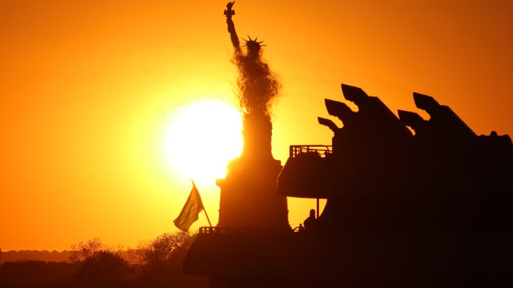 The sun sets behind the Statue of Liberty as it is partially obscured by heat waves from the exhaust of a passing ferry on May 31, 2020 in New York City.