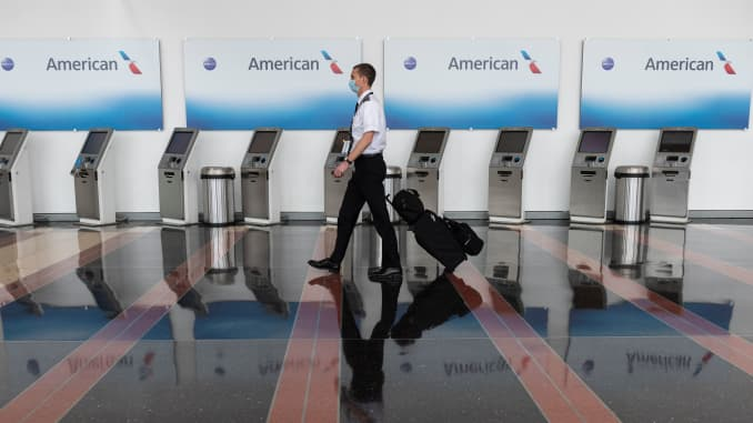 An airline employee walks past empty American Airlines check-in terminals at Ronald Reagan Washington National Airport in Arlington, Virginia, on May 12, 2020.