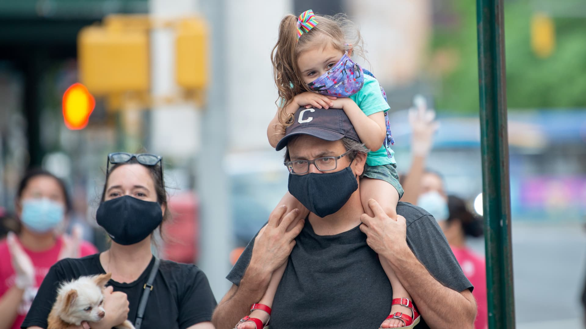 A small child wearing a mask sits on her fathers shoulders outside of the Lenox Health Greenwich Village hospital during the nightly 'Clap Because We Care' cheer for medical staff and essential workers on May 29, 2020 in New York City.