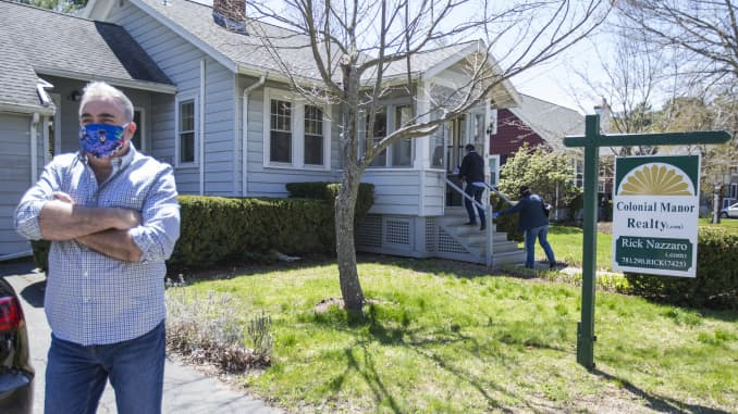 "Rick Nazarro of Colonial Manor Realty waits in the driveway as a couple enters a property he is trying to sell during a ""controlled"" open house on May 2, 2020 in Revere, MA."
