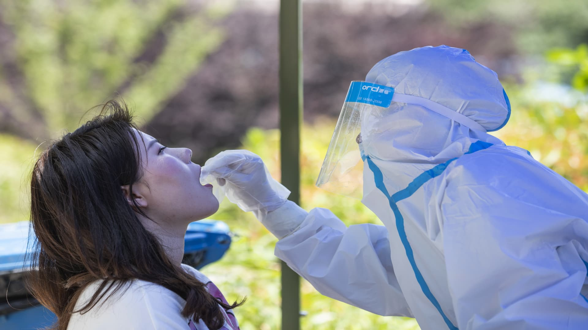 A medical worker takes a swab sample from a student to be tested for the Covid-19 coronavirus at Wuhan University, on the first day of classes in Wuhan on June 8, 2020.