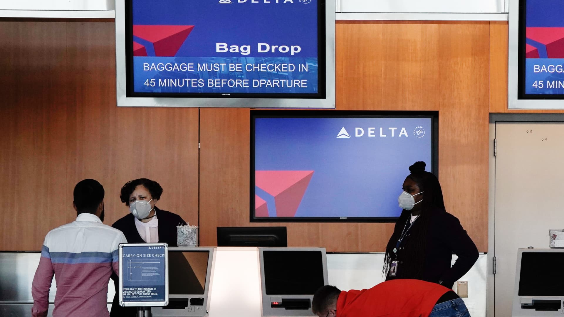 Gate agents assist travelers at a Delta Air Lines Inc. bag drop counter at the San Diego International Airport (SAN) in San Diego, California, U.S., on Monday, April 27, 2020.