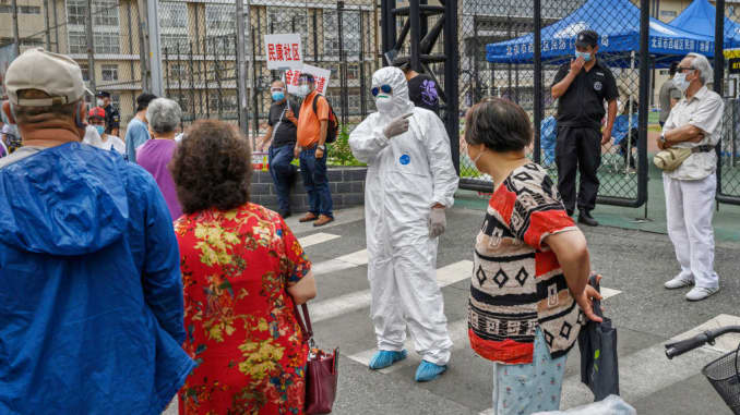 A Chinese epidemic control worker wears a protective suit and mask as he and volunteers direct people at a site where authorities were performing nucleic acid tests for COVID-19 on citizens who have had contact with the the Xinfadi Wholesale Market or someone who has, at an outdoor sports center June 15, 2020 in Beijing, China.