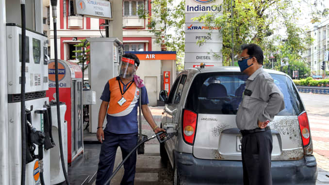 An Indian Oil Petrol Pump employee is seen wearing a face shield, as he fuels a customer's vehicle in an open Petrol Retail Outlet of Kolkata during the Covid-19 pandemic.