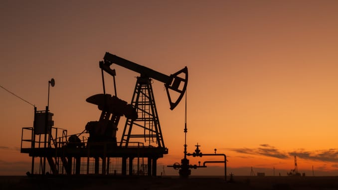 The silhouette of an oil pump is seen at sunset.