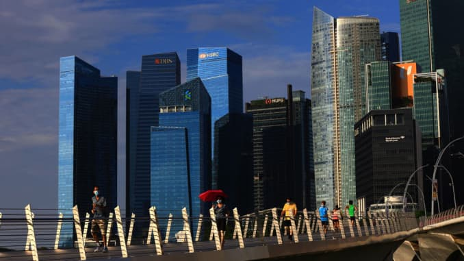 People wearing protective masks walk along the Jubilee Bridge at the Marina Bay waterfront on June 7, 2020 in Singapore.