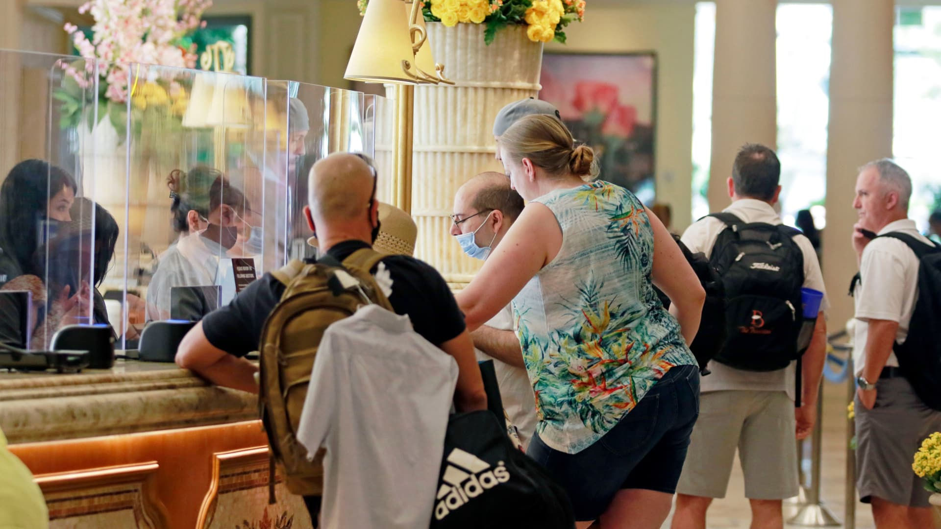 Workers assists guests at check-in during the reopening of Bellagio hotel-casino on June 4, 2020, in Las Vegas.