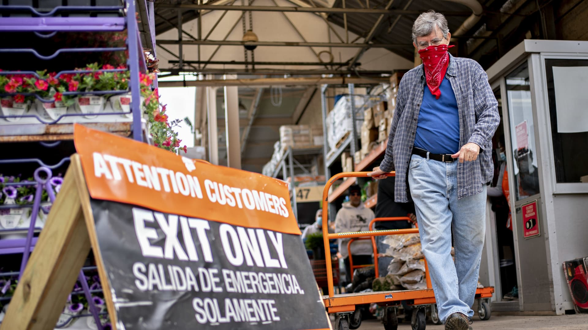 A customer wears a protective mask while pulling a cart outside a Home Depot Inc. store in Reston, Virginia, U.S., on Thursday, May 21, 2020.